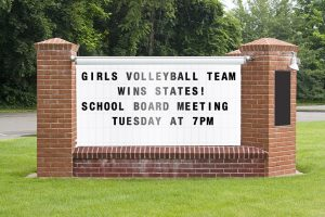 A school billboard that says girls team won states and school board meets tuesday at 7