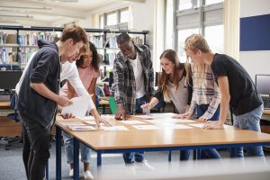 Group Of High School Students Collaborating On Project In Library