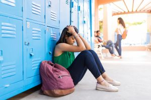 Stressed college student with hands in hair sitting against lockers