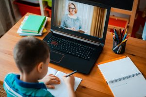 Distance learning online education. A schoolboy boy studies at home and does school homework. A home distance learning