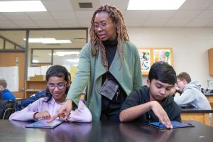 A teacher helps students during a coding lesson at Sutton Middle School.
